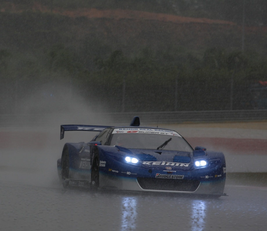Fast cars and motorcycles in the rain