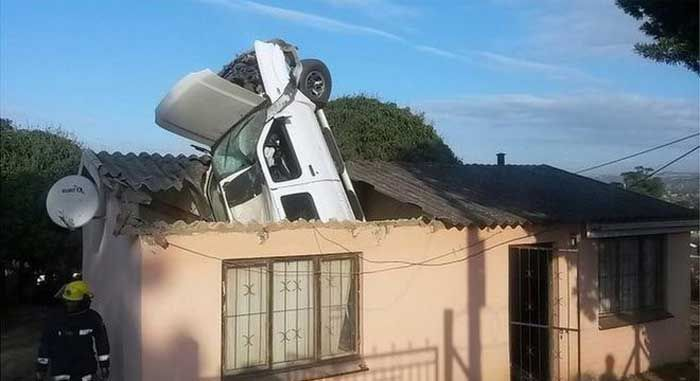 Car Lands Engine First In The Roof Of A House