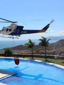 Firefighting Helicopter Refills A Basket With Water From A Swimming Pool