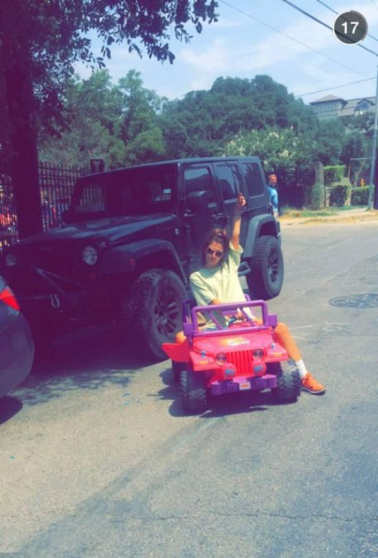 A College Student Rides Around Campus In A Barbie Jeep