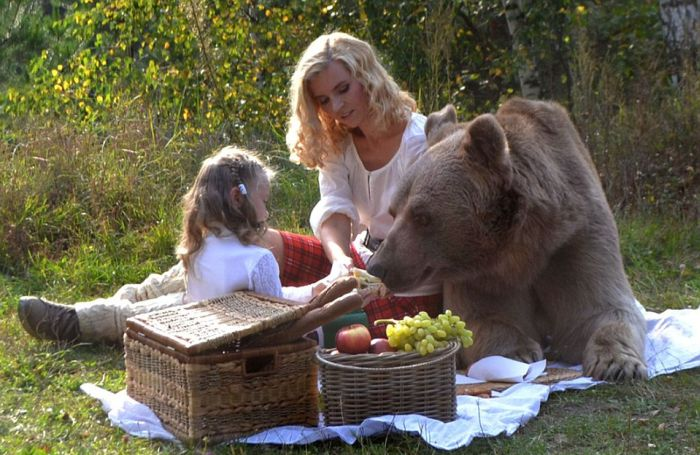Mother And Daughter Enjoy An Outdoor Picnic With A Giant Bear