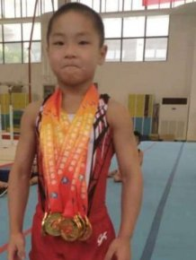 Seven Year Old Chinese Kid Shows Off His Eight Pack After Winning Medals