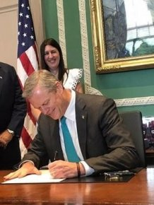 The Governor Of Massachusetts Smiles As He Signs Off On New Law