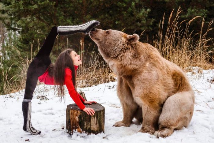 Gymnast Poses With A Brown Bear