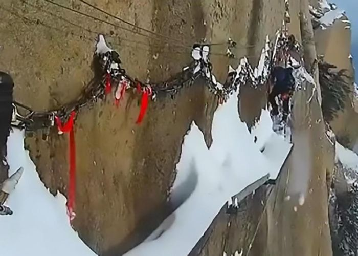 Workers Sweep Snow From A Cliff Path
